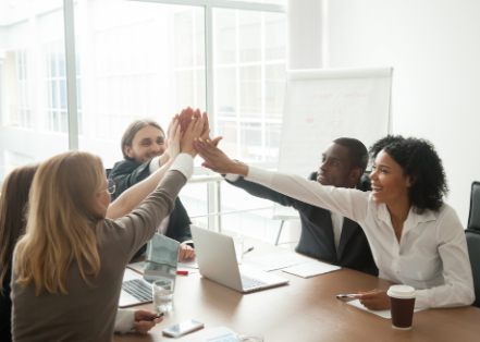Team High Five at Conference Room Table