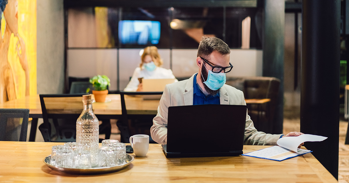 Man at computer wearing a mask